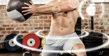 Muscular man exercising with medicine ball against fitness inter